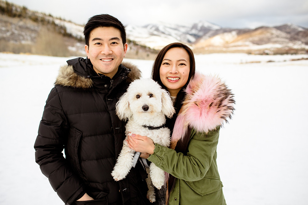 couple in winter jackets hold their dog in front of snowy utah mountains