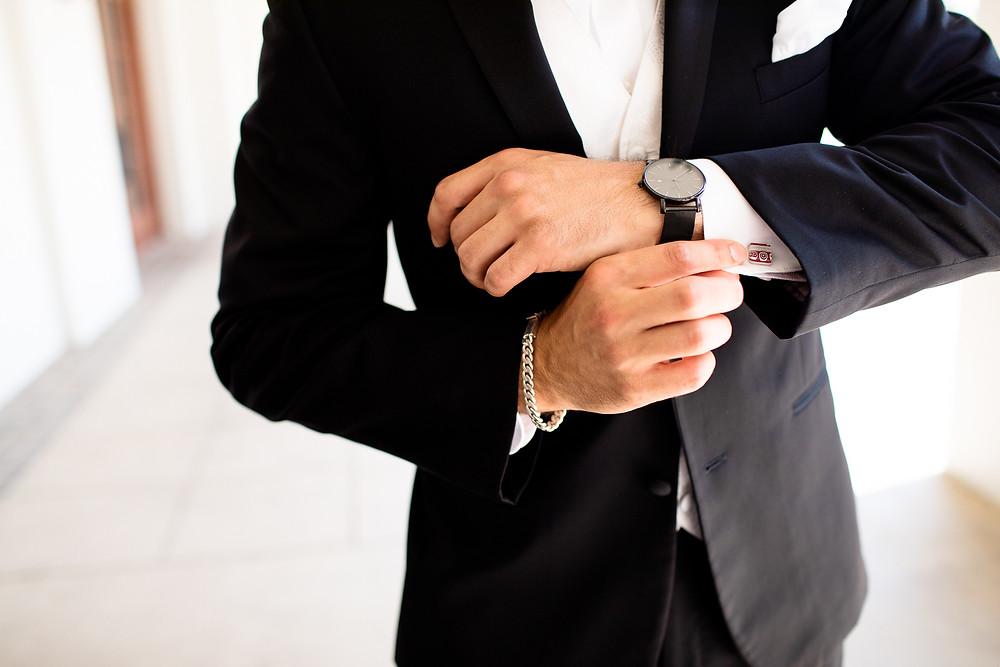 groom adjusting his silver cufflinks