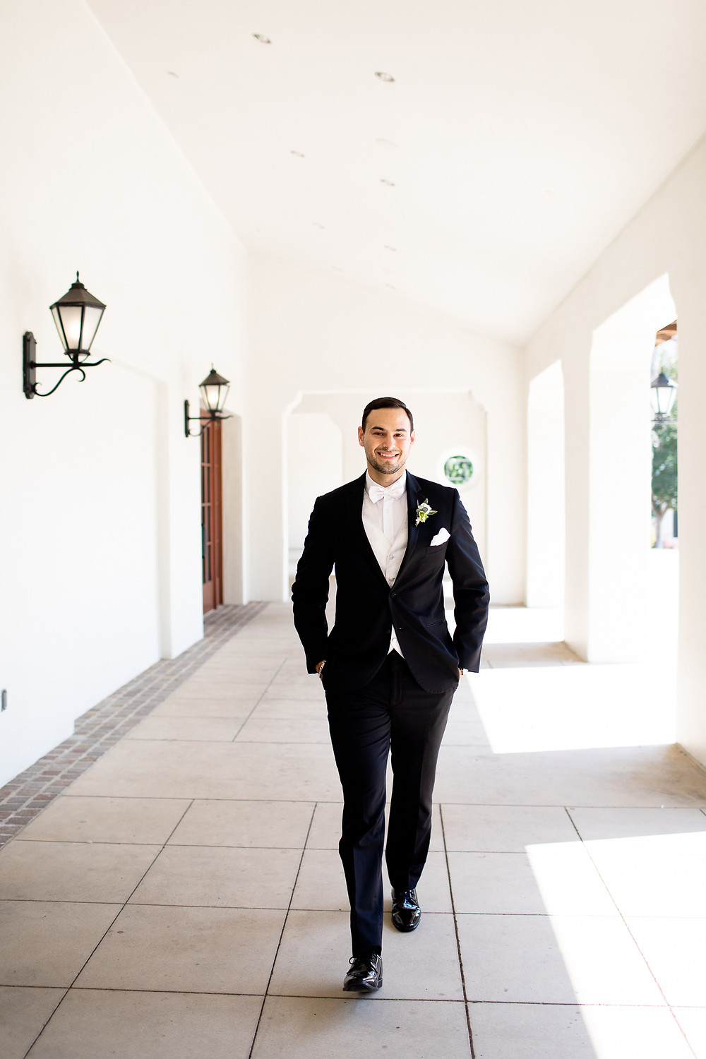 groom smiling and walking towards the camera