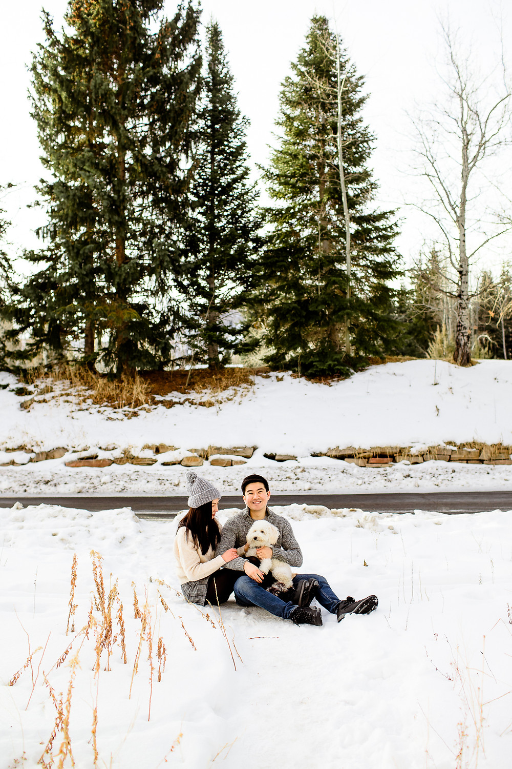 cute couple playing with their dog in the utah snow