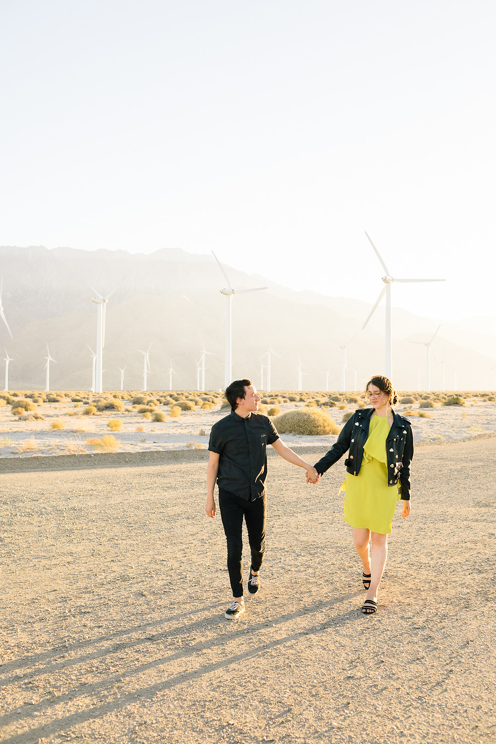 couple in fancy clothes walking in front of palm springs windmills