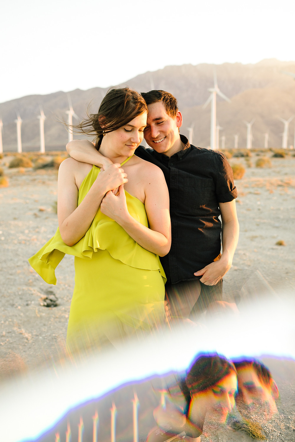 couple snuggling in front of palm springs windmills at golden hour