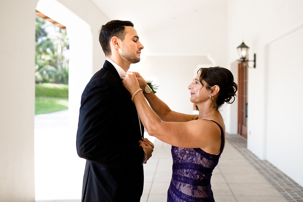 mother of the groom adjusting the groom's bowtie