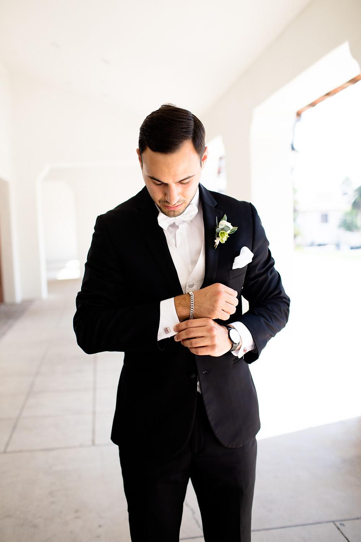 groom adjusting silver cufflinks at ritz carlton santa barbara