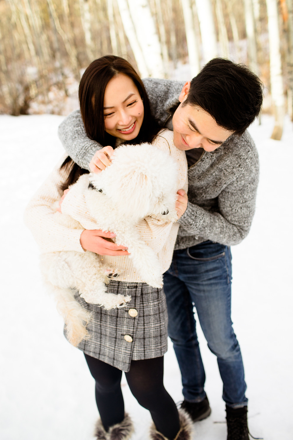 man and woman playing with their dog at a snowy park