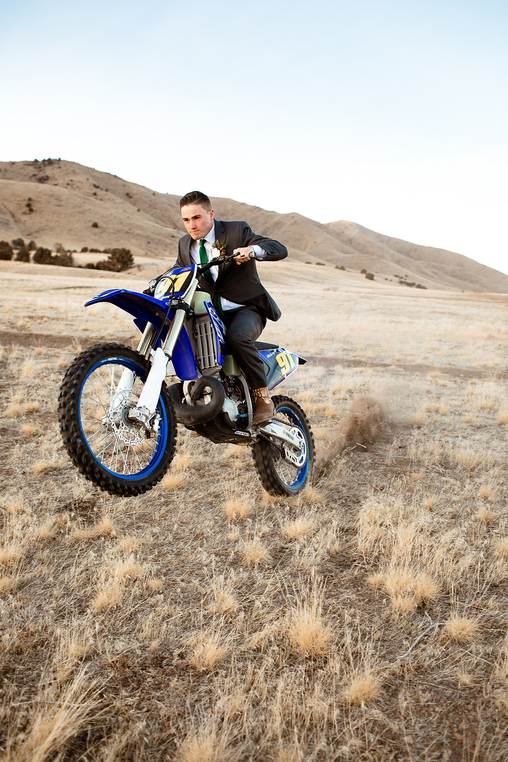 groom popping dirtbike wheelies on his wedding day in his suit
