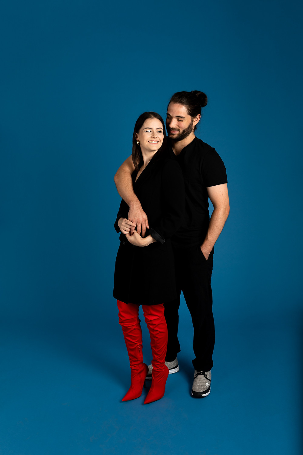 cute couple in a blue studio with man's arm around woman's shoulder, both man and woman smiling at each other