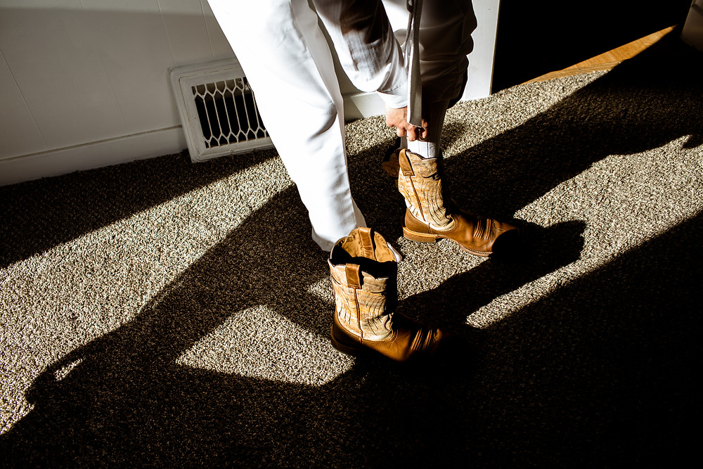 groom putting on brown cowboy boots