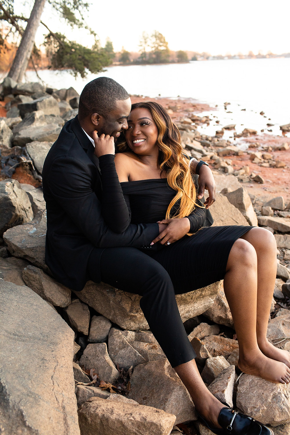 woman smiling and holding on her fiance's face while sitting on the rocky lakeshore