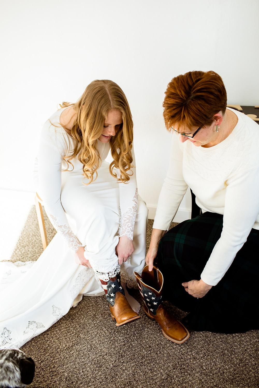 bride's mom helping bride into cowboy boots