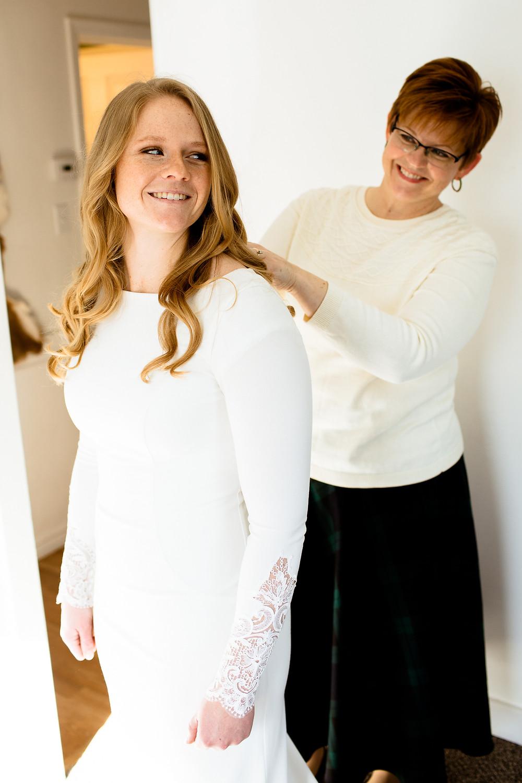 bride's mom helping zip up bride's wedding dress