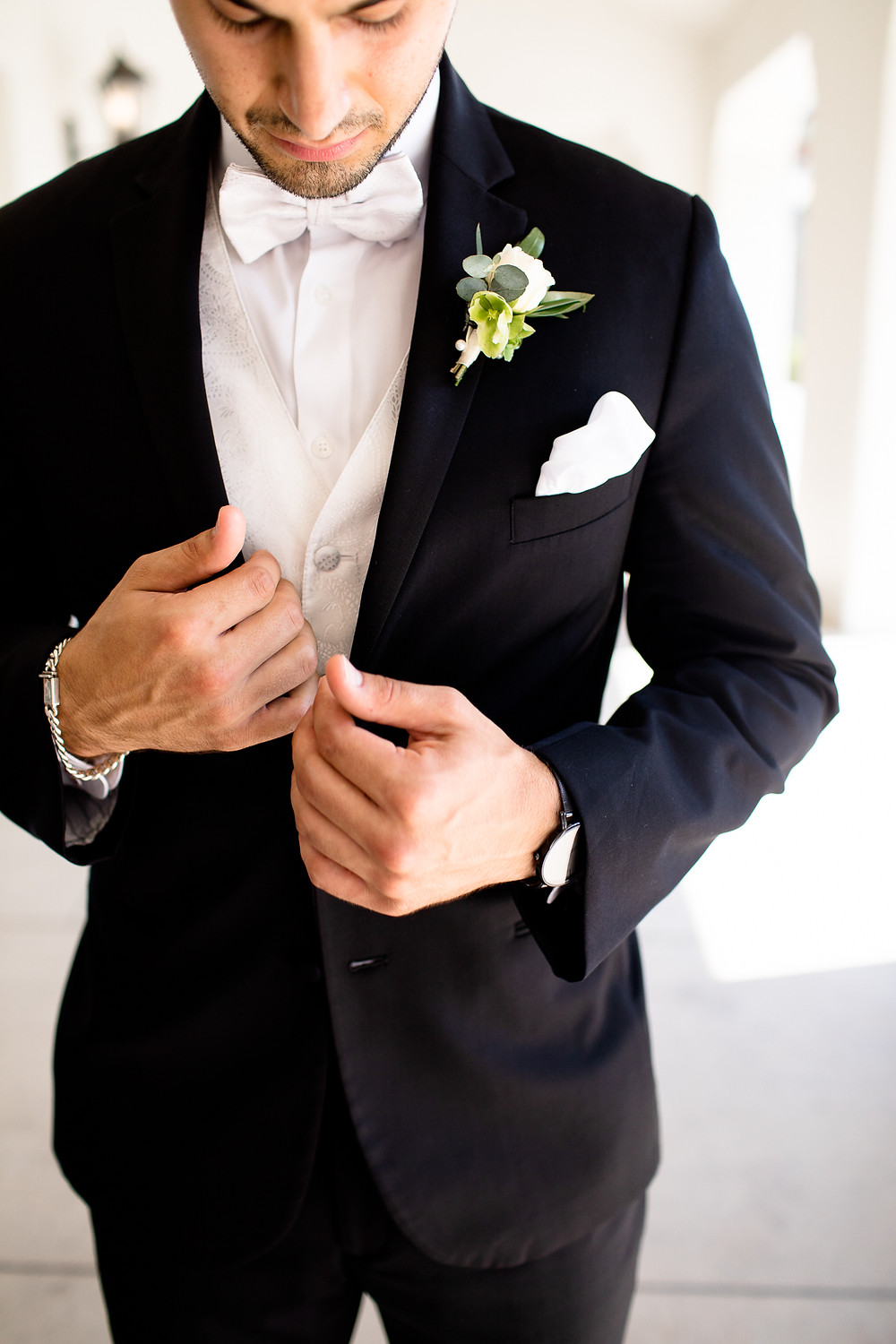 groom buttoning up his tux with rose boutonnière