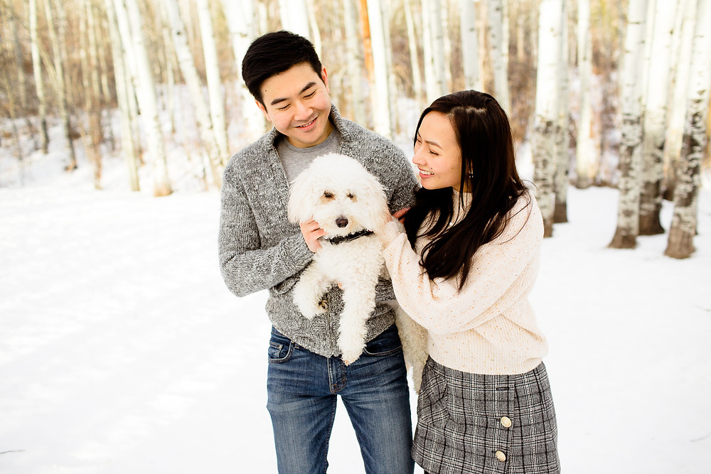 couple in Park City snow play with their puppy