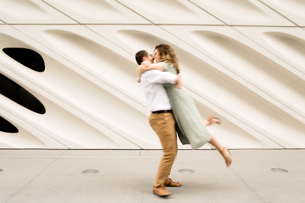 blurry photo of couple spinning in front of broad museum