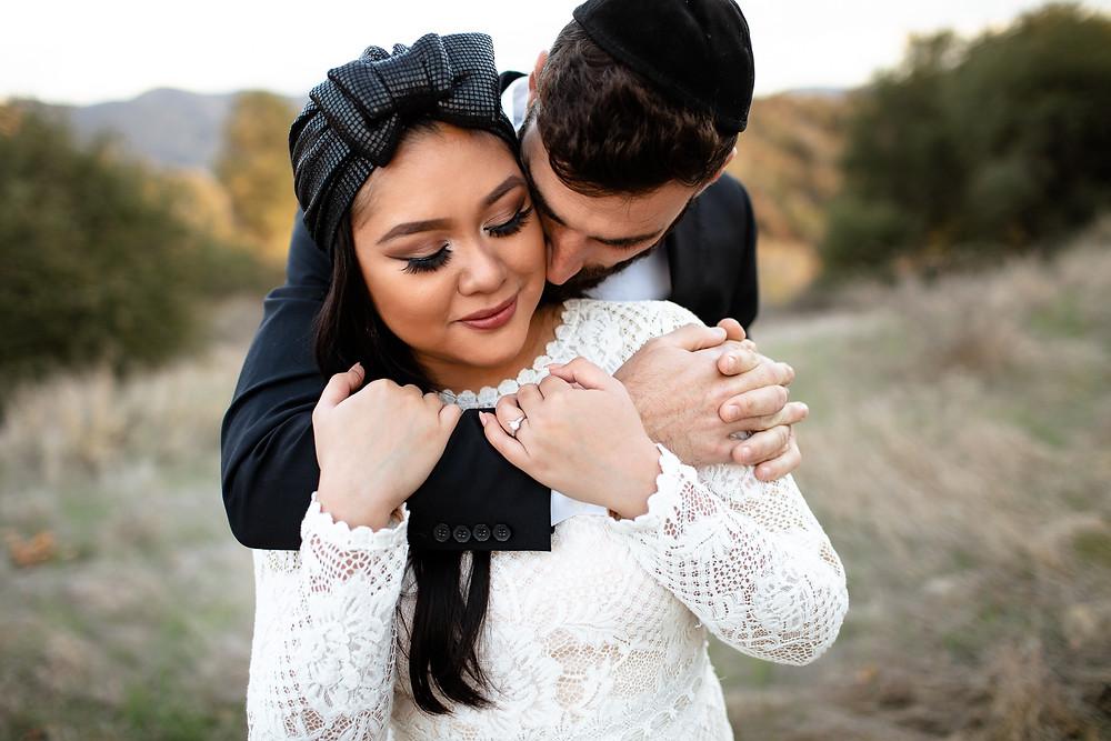 groom in yamalka cuddling bride in head wrap