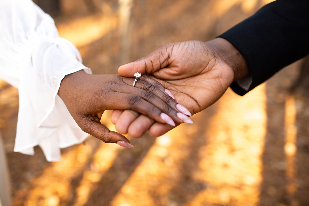 black couple holding hands with autumn leaves behind them