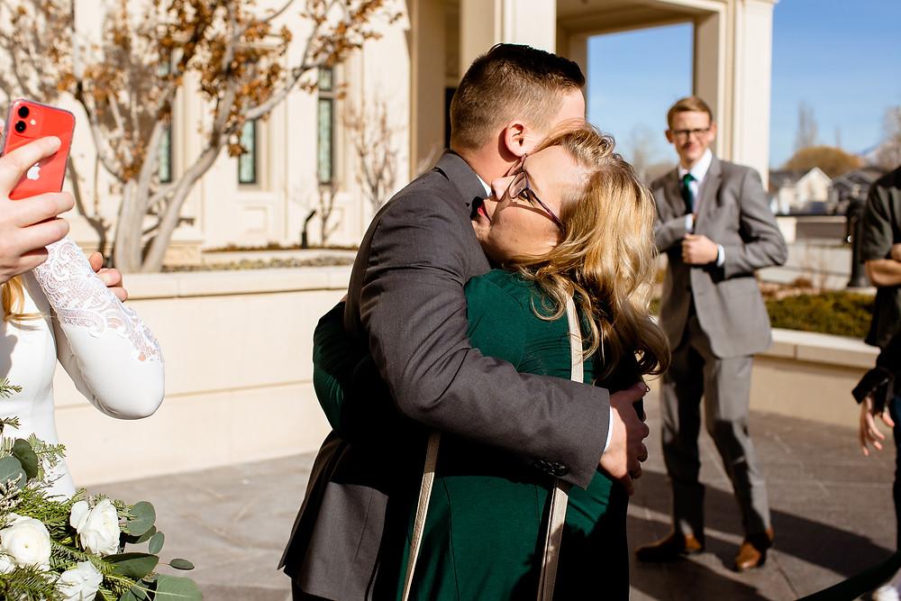 groom hugging mom after wedding ceremony