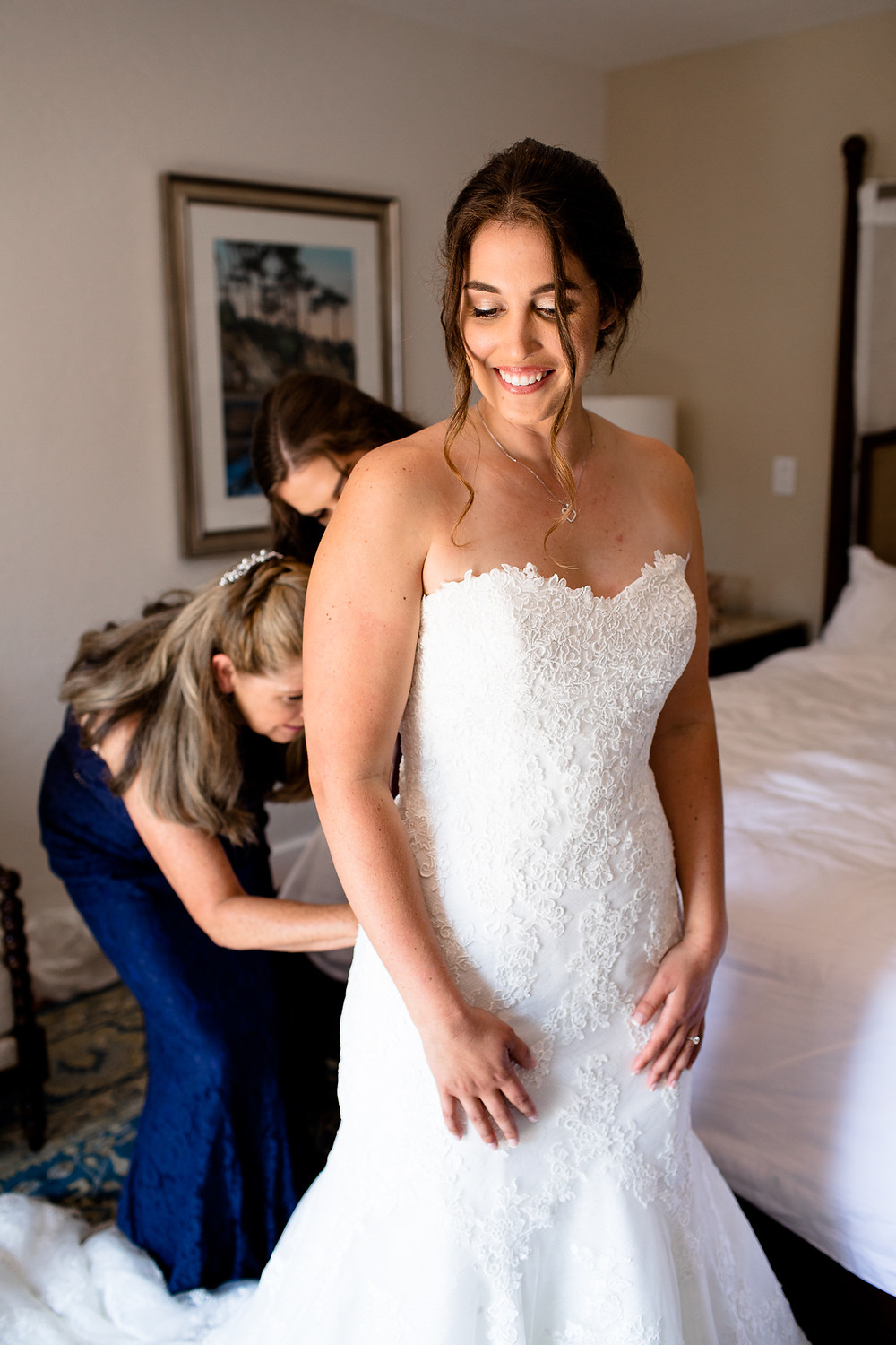 bride getting zipped up in wedding dress