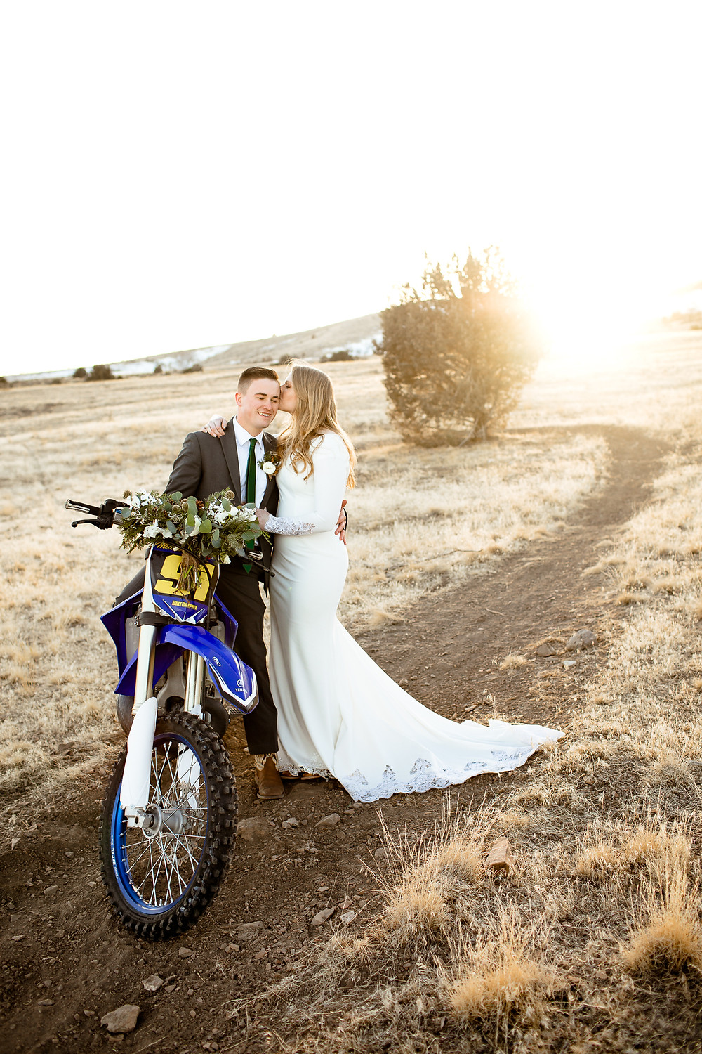 bride kissing her groom's face while he sits on a dirtbike