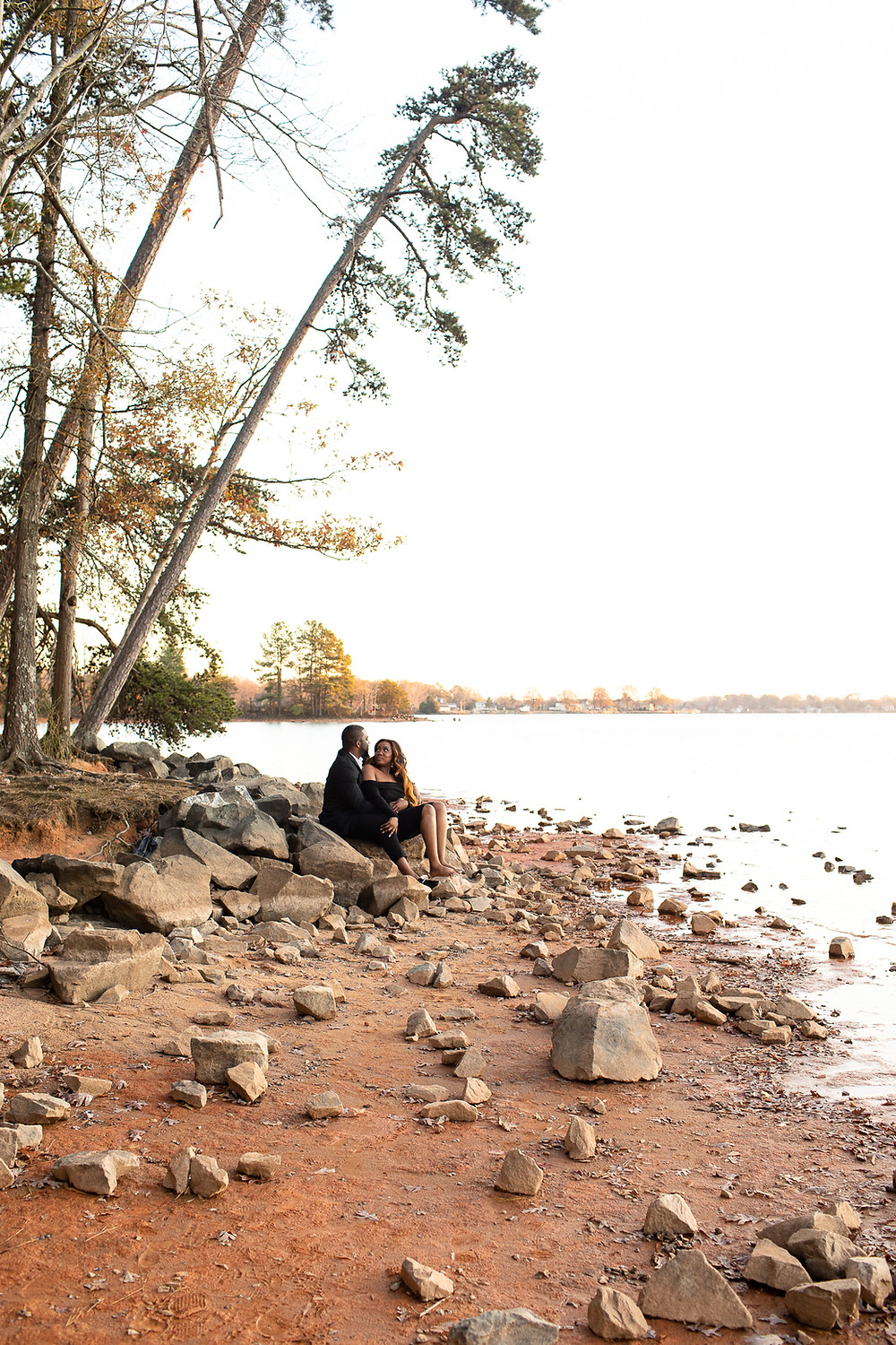 man and woman sitting on rocky lake shore of lake norman at jetton park