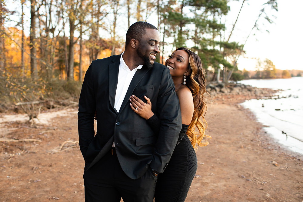man and woman dressed in all black smiling at each other on the banks of lake norman