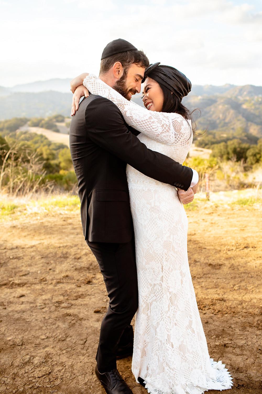 jewish bride and groom hug and laugh