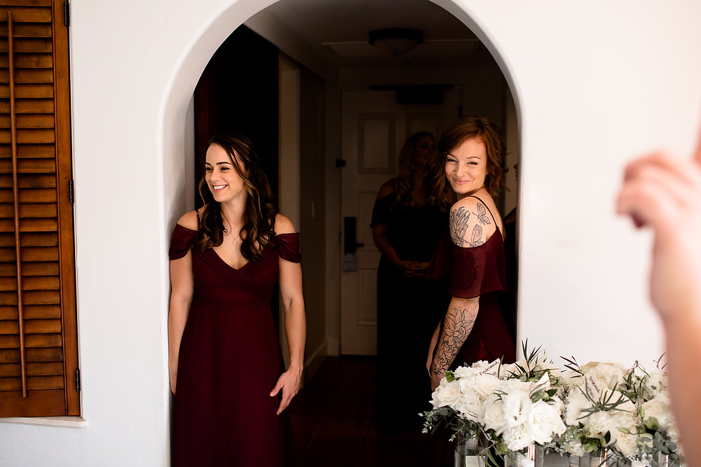 two bridesmaids smiling at bride getting ready