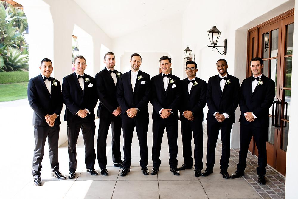 groomsmen in all black tuxedos smiling