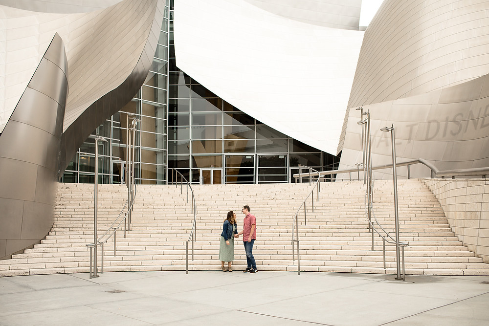 wide shot of man and woman laughing in front of the walt disney concert hall