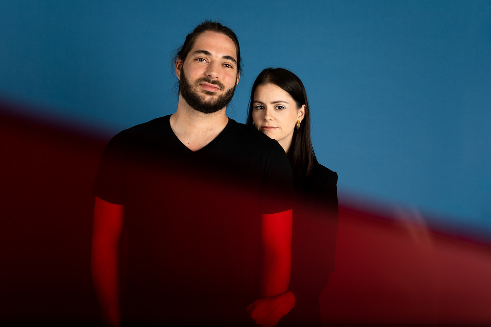 man and woman in front of blue background with red film in front of them