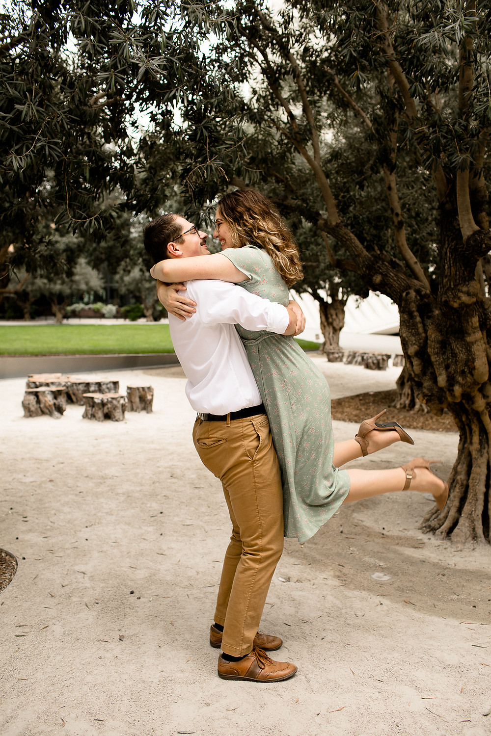 man picking up woman in green dress in front of trees