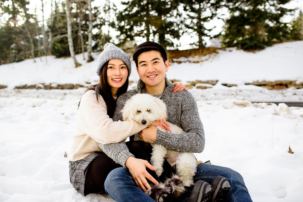 man and woman sitting in the snow and holding their dog