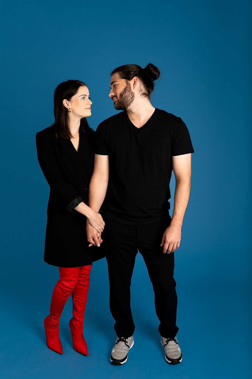 guy in all black and girl in black dress and red boots holding hands and looking at each other