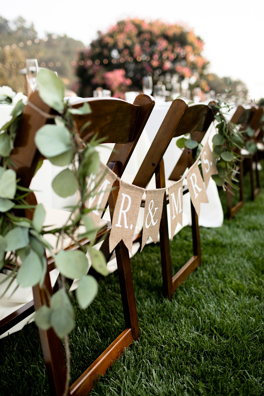 mr and mrs sign hanging on the back of the bride and groom's chairs at the sweetheart table at santa barbara reception
