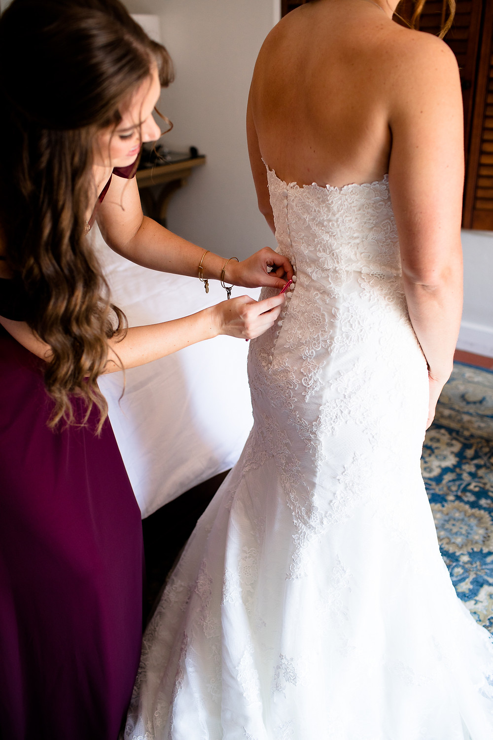 maid of honor buttoning up wedding dress