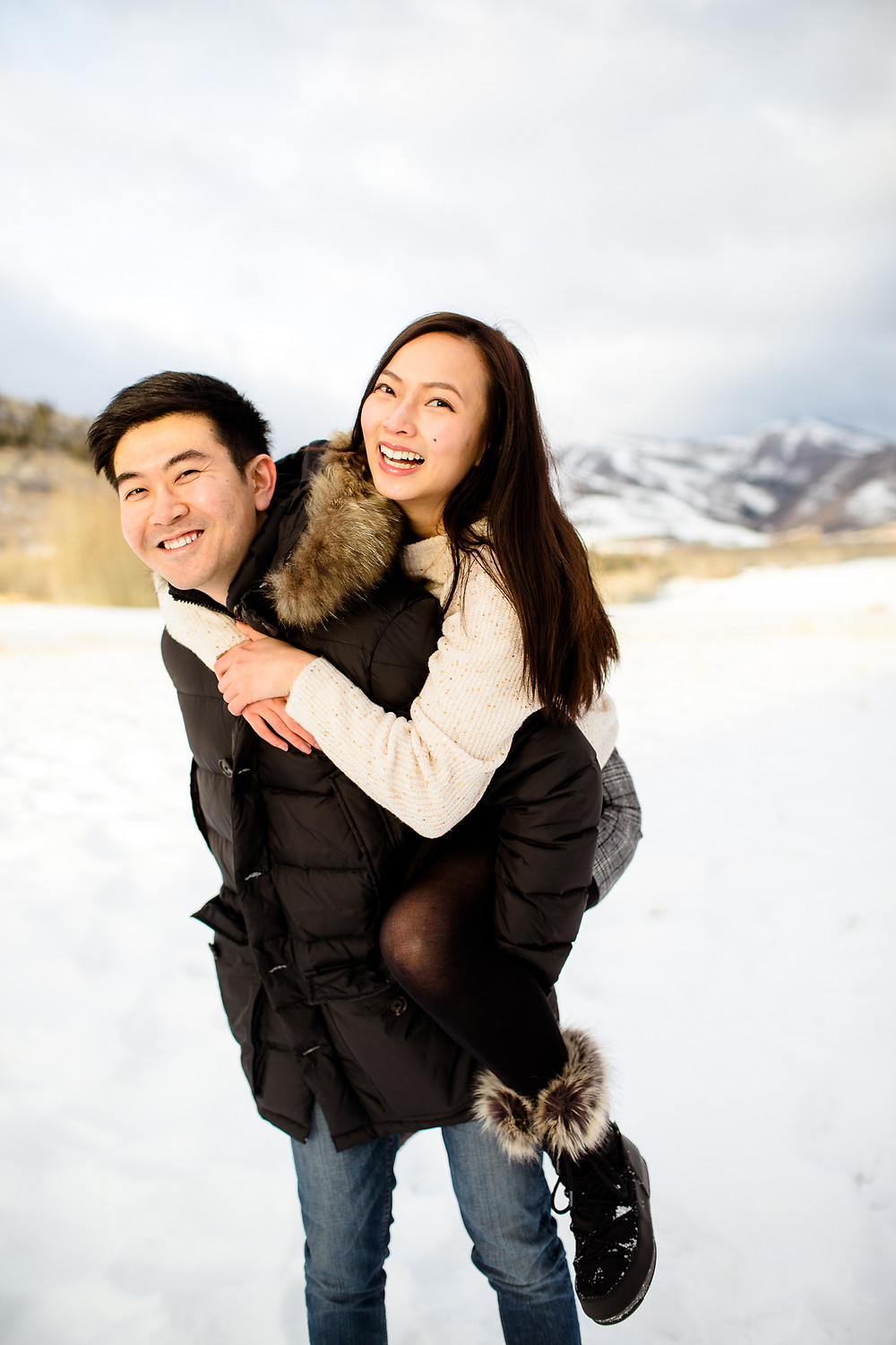 man gives woman a piggyback ride in park city utah