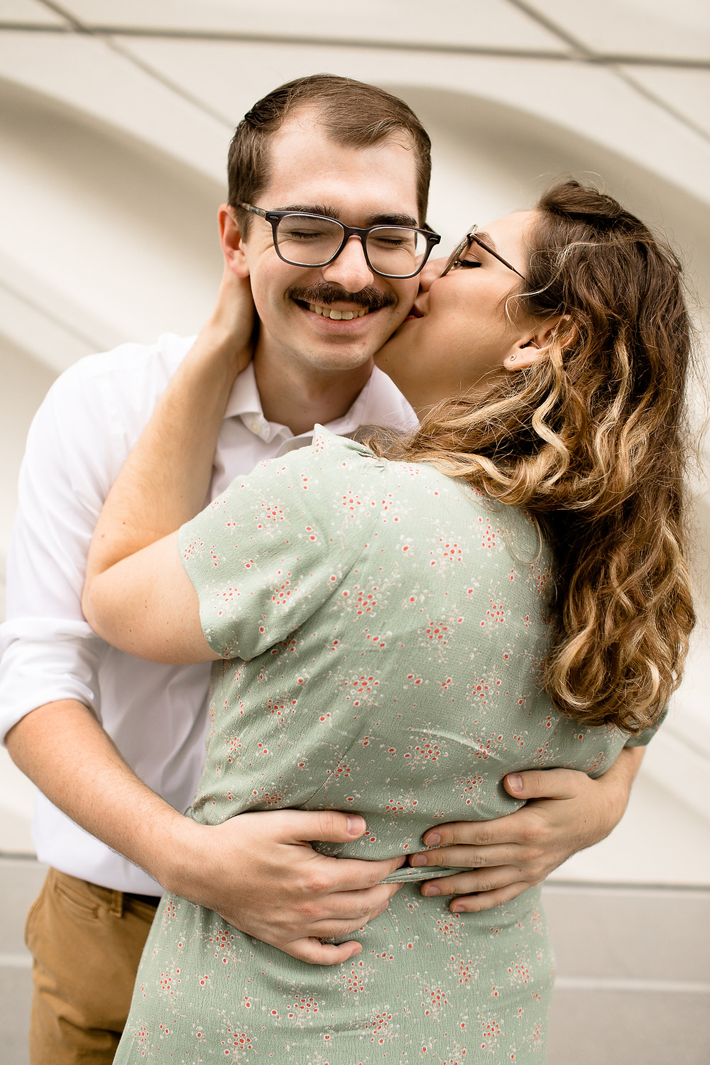 woman kissing man on the cheek and the man smiling