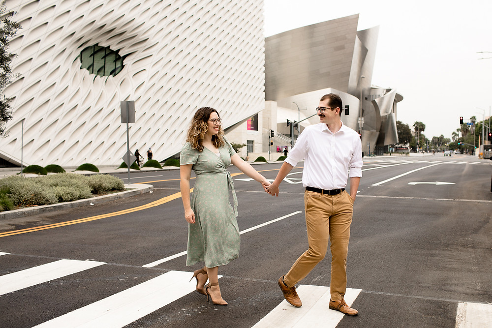 man and woman holding hands in crosswalk with the broad museum and walt disney concert hall in the background