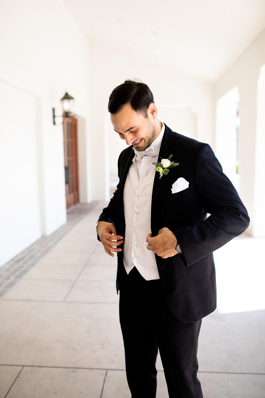 groom buttoning up his tux on his wedding day at the ritz carlton bacara santa barbara