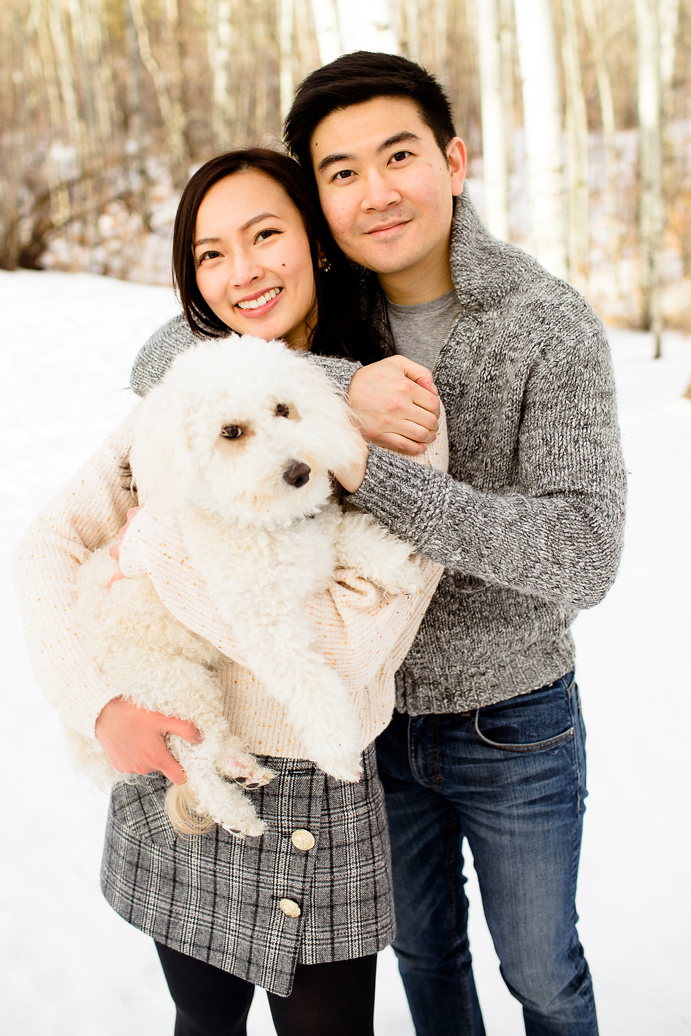 couple and dog smiling at the camera