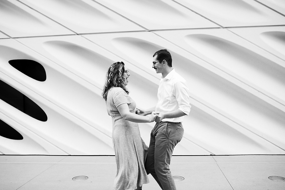 couple dancing and laughing in front of the broad museum, black and white photo