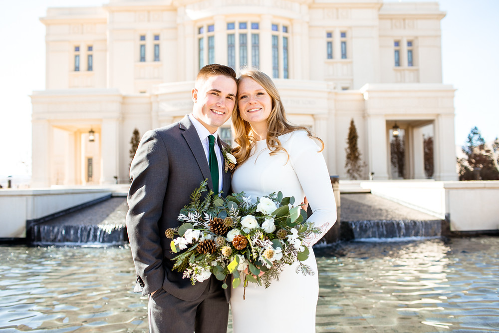 bride and groom smiling in front of payson, utah temple
