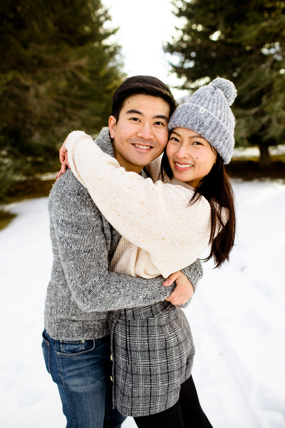 man and woman smiling at the camera in front of snowy pine trees
