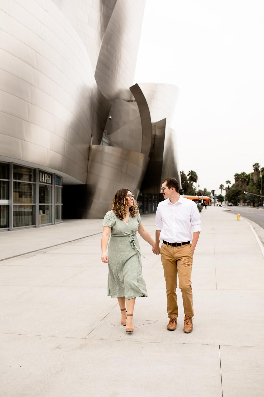 couple walking past walt disney concert hall on streets of dtla