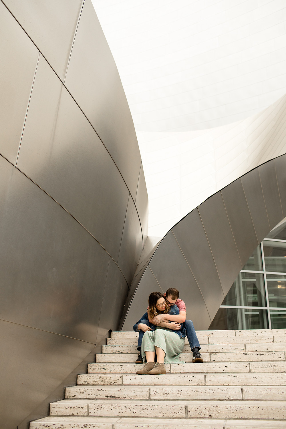 couple cuddling while sitting on steps of the walt disney concert hall in downtown los angeles