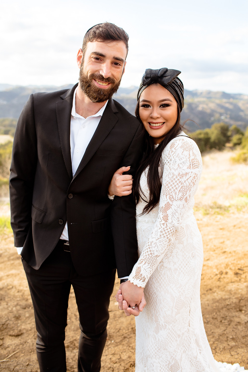 jewish bride and groom smiling at the camera in topanga canyon state park
