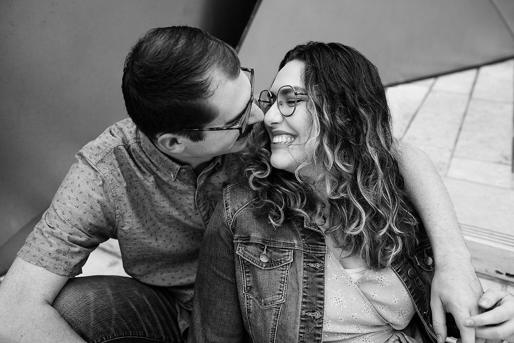 man and woman nuzzling noses while sitting down black and white photo