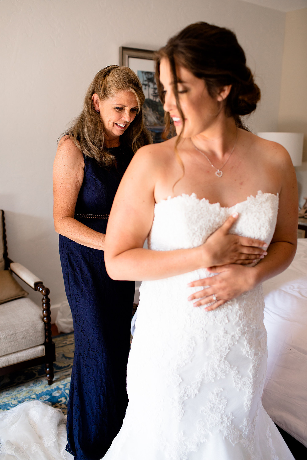 mom helping her daughter into her wedding dress