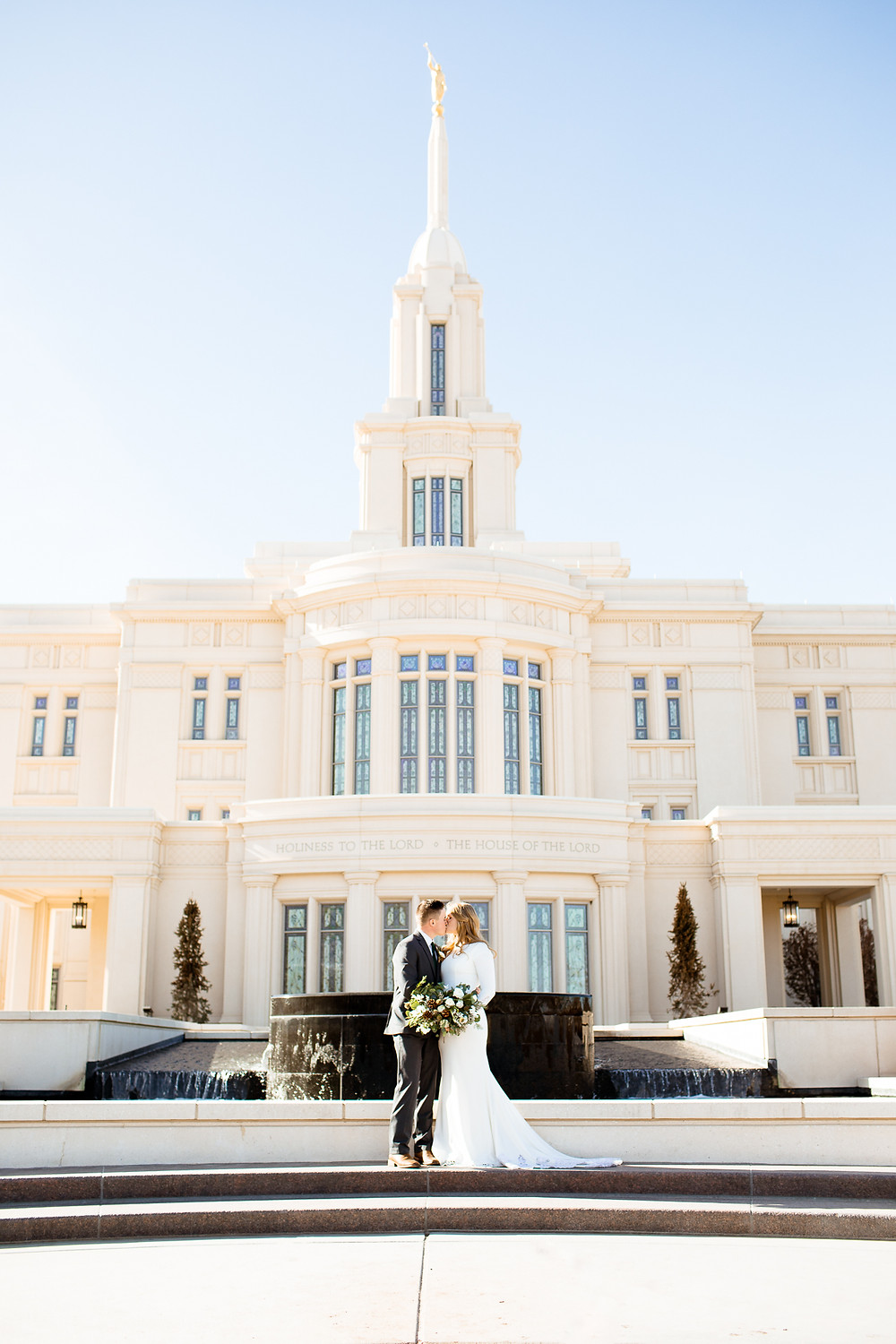 bride and groom kiss in front of payson utah temple