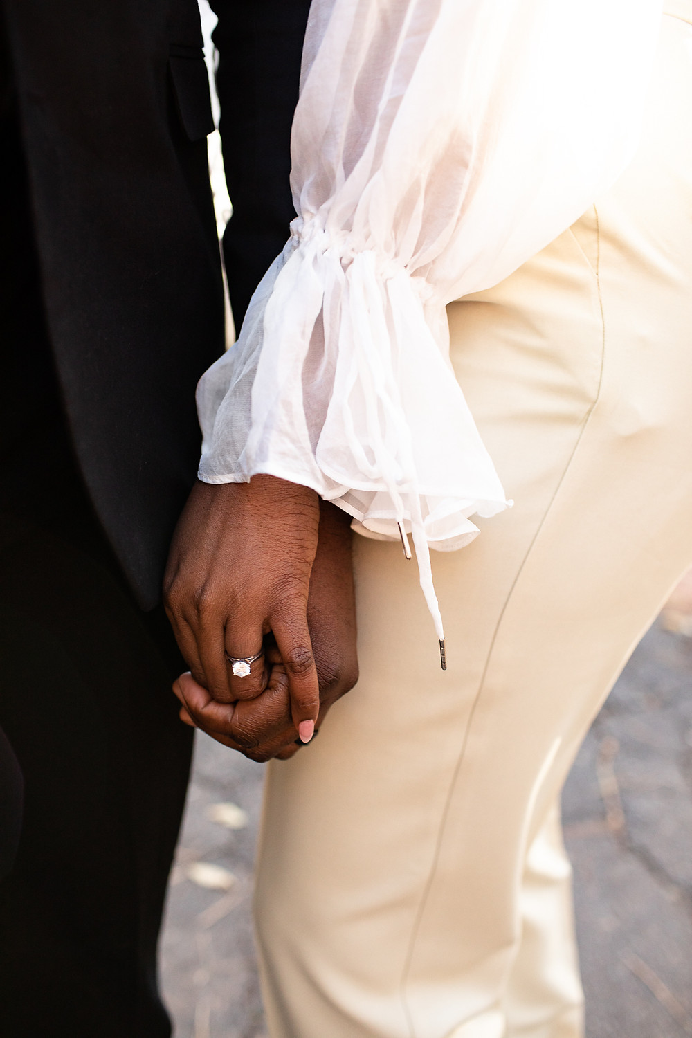 man in a black suit and a woman in a white blouse holding hands with an engagement ring on